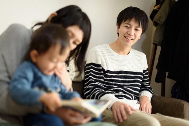 絵本を読む男の子とお母さんを見つめるお父さん