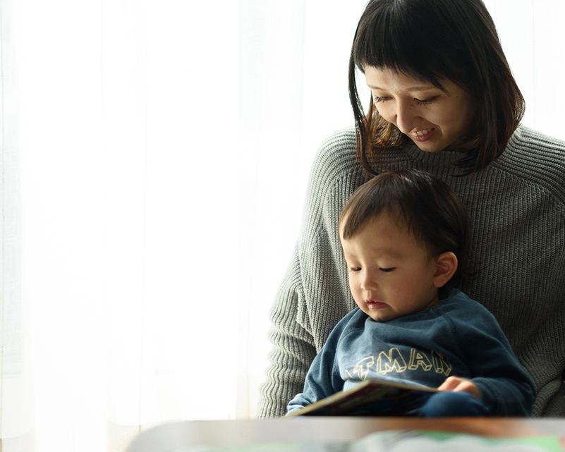 お母さんに絵本を読んでもらう男の子
