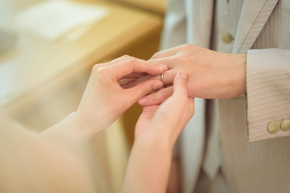 新郎に指輪をはめる新婦の手元