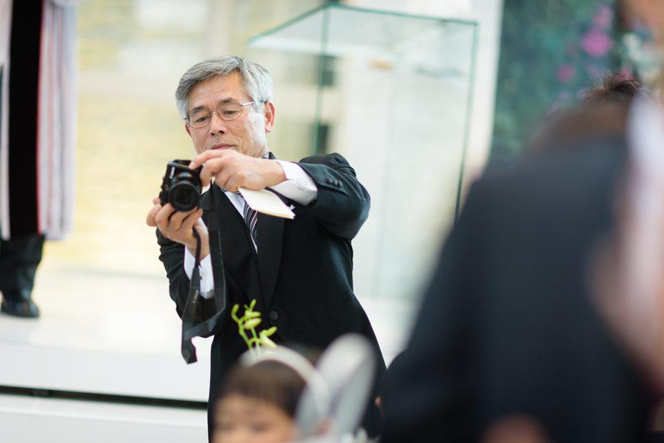 退場する新郎新婦の背中にカメラを向けるお父さん