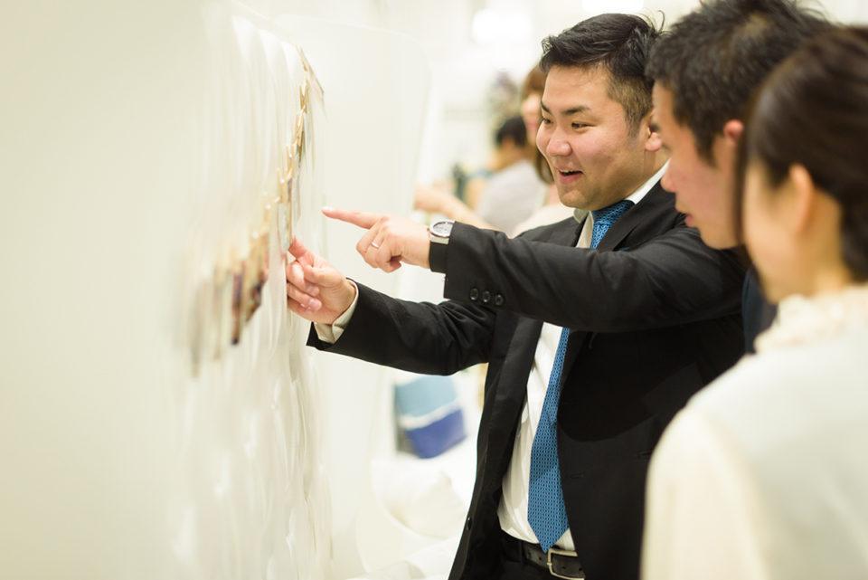 壁に飾られた写真を指差す男性ゲスト