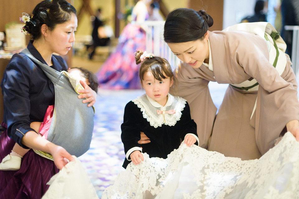 新婦のドレスの裾を握る女の子
