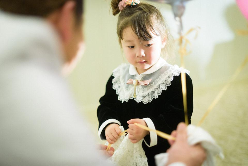ドレスの裾を握ったままバルーンを受け取る女の子