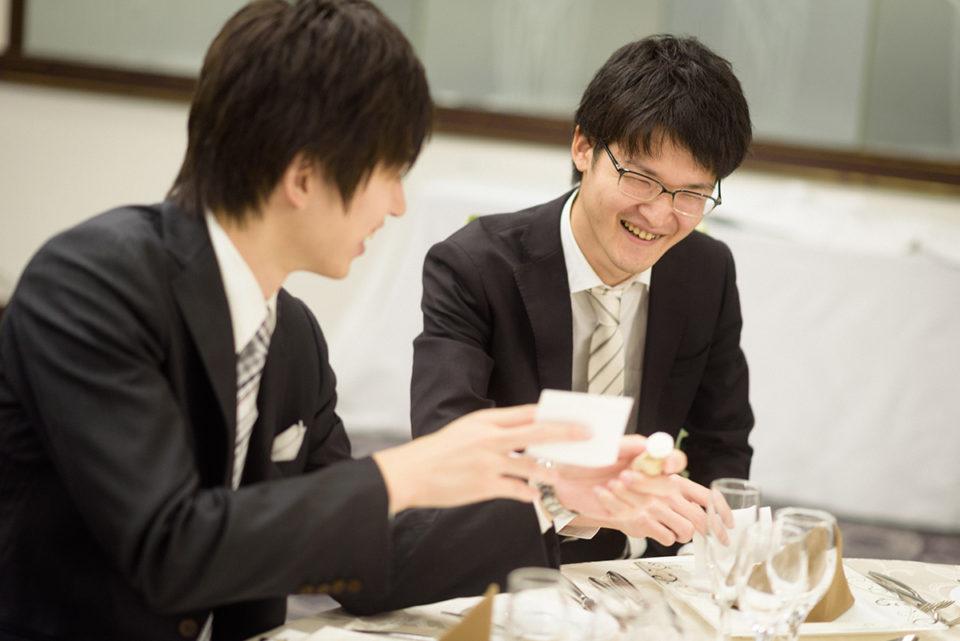 テーブルに用意されたメッセージカードを見て笑う男性ゲスト