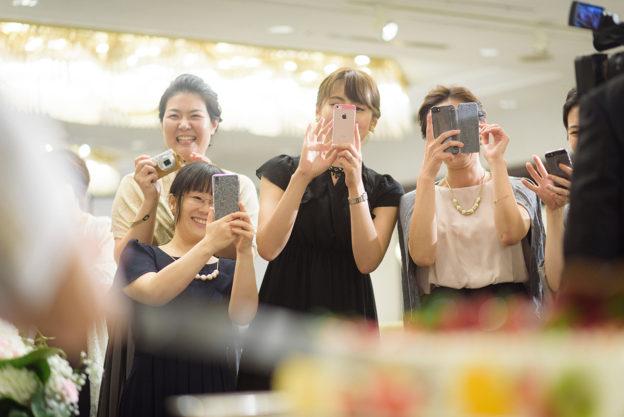ケーキカットをする新郎新婦にカメラを向ける女性ゲスト