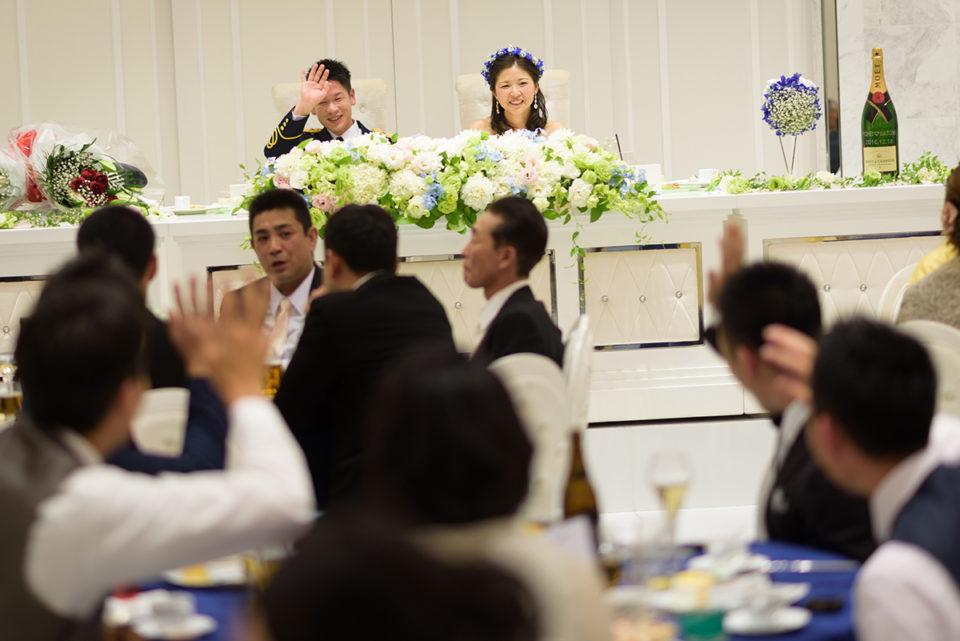 ゲストテーブルに向かって手を振る新郎