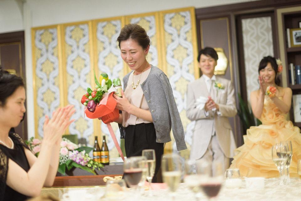 野菜のブーケを手に笑顔で席に戻る女性ゲスト