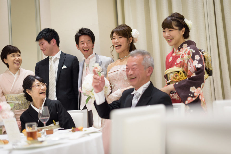 家族と記念撮影をして大笑いをする新郎新婦