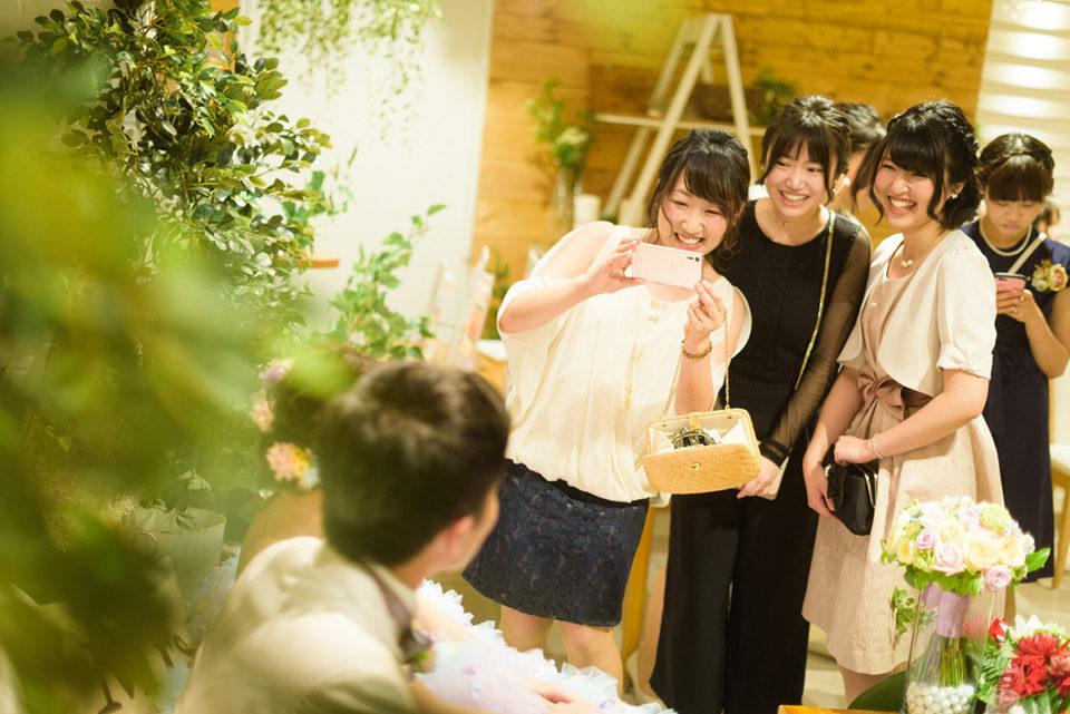 高砂の新郎新婦にカメラを向ける女性ゲスト