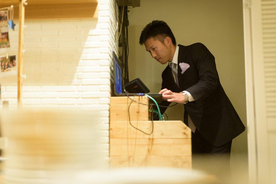 二次会でパソコンを操作する男性ゲスト