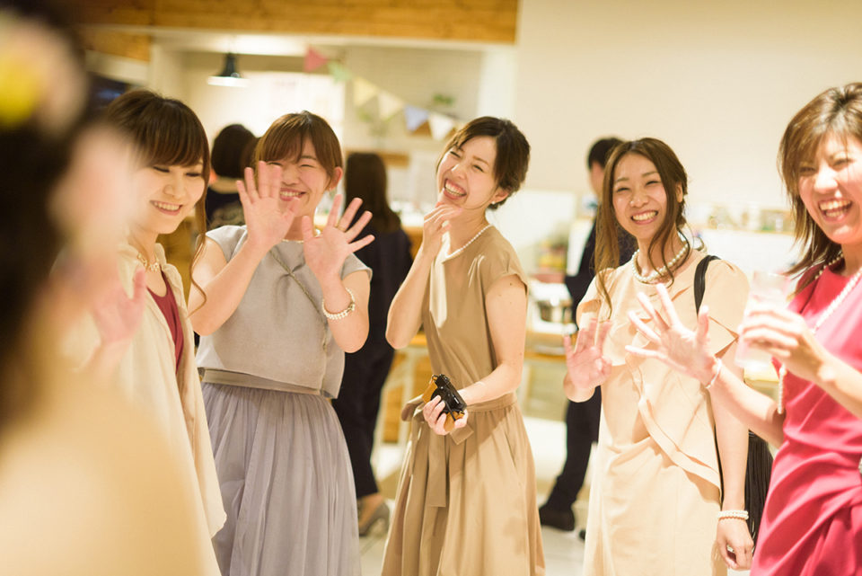 新婦に笑顔で手をする女性ゲスト