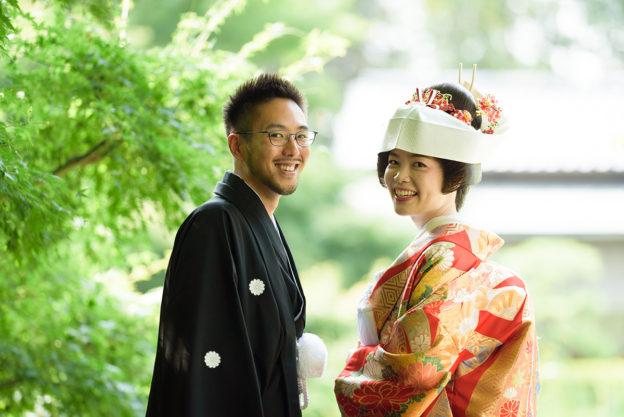 ホテルニューオータニの庭園でカメラを見て笑う和装の新郎新婦