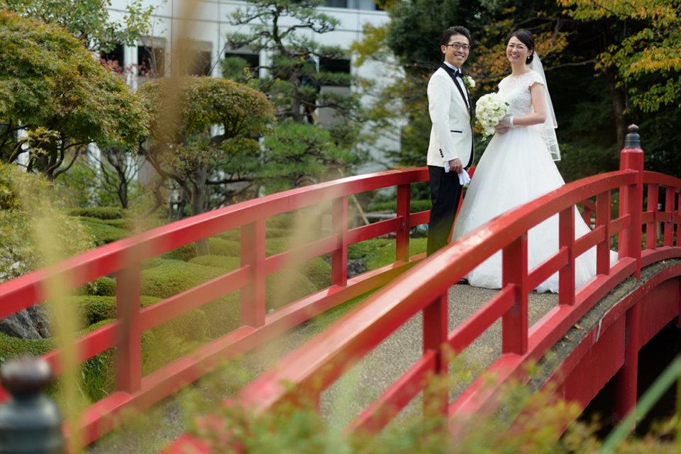 ホテルニューオータニの庭園の赤い橋に立つ新郎新婦