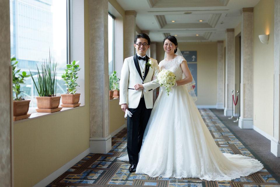 ホテルニューオータニの廊下で記念撮影をする新郎新婦