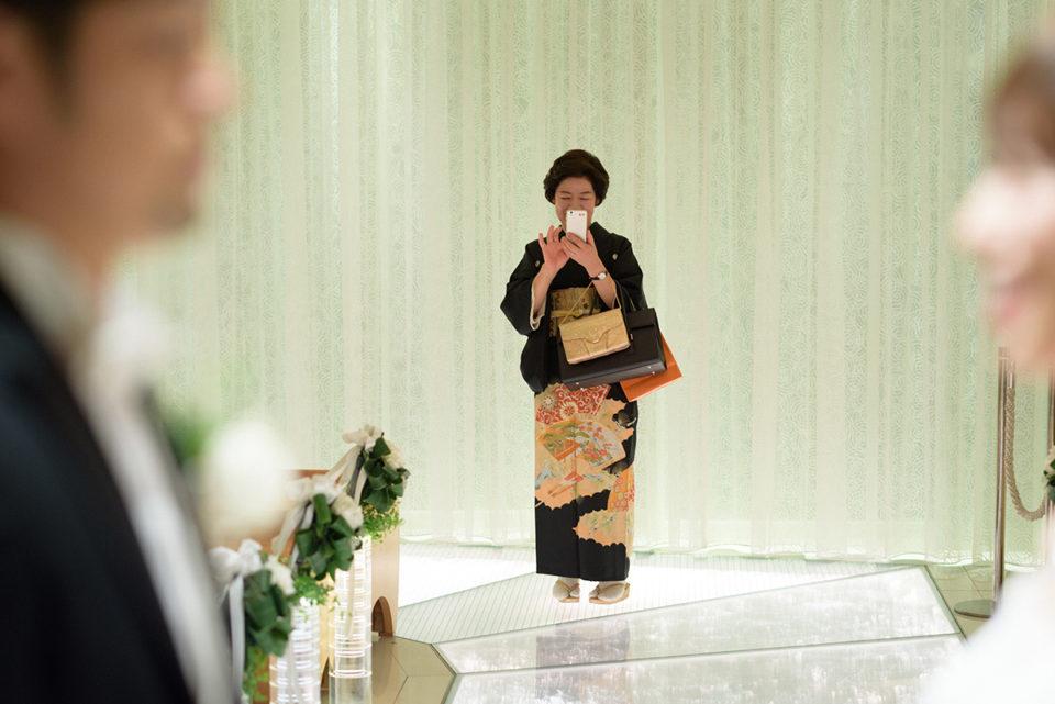 ヒルトン東京での挙式リハーサル中に新郎新婦を撮るお母さん