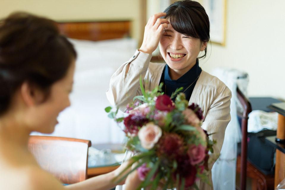 ブーケを新婦に手渡す友人女性