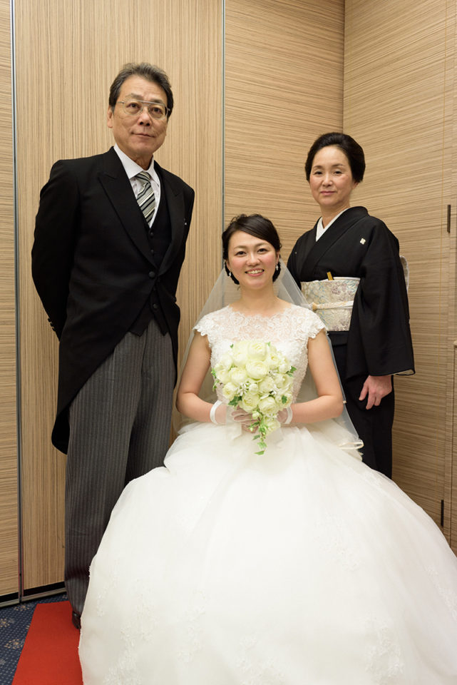 親族控室で家族写真を撮る新婦