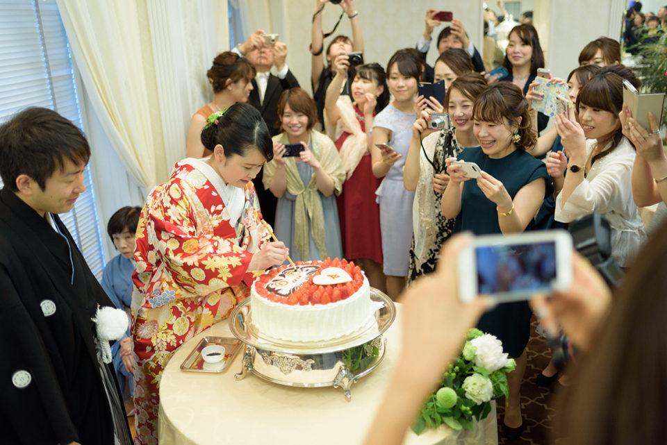 東京大神宮のダルマケーキに目を入れる新婦