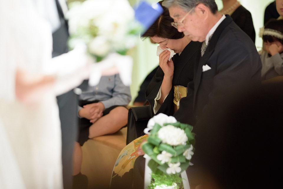 挙式中に涙をこらえるお母さん