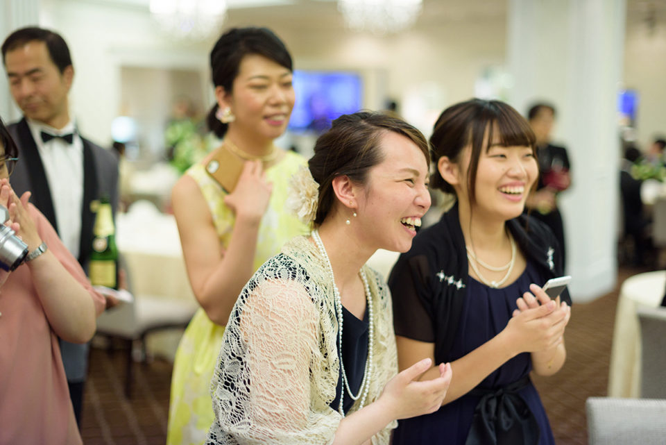 新郎新婦のファーストバイトを笑顔で見つめる女性ゲスト