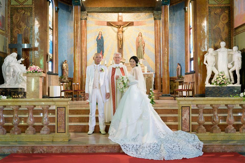 サレジオ教会の挙式後に司祭と記念撮影をする新郎新婦