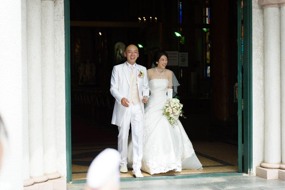 教会の外でゲストに迎えられる新郎新婦