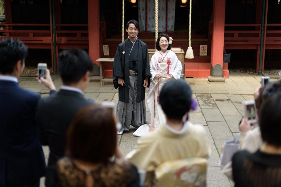 挙式後に赤坂氷川神社の前でゲストに囲まれる新郎新婦