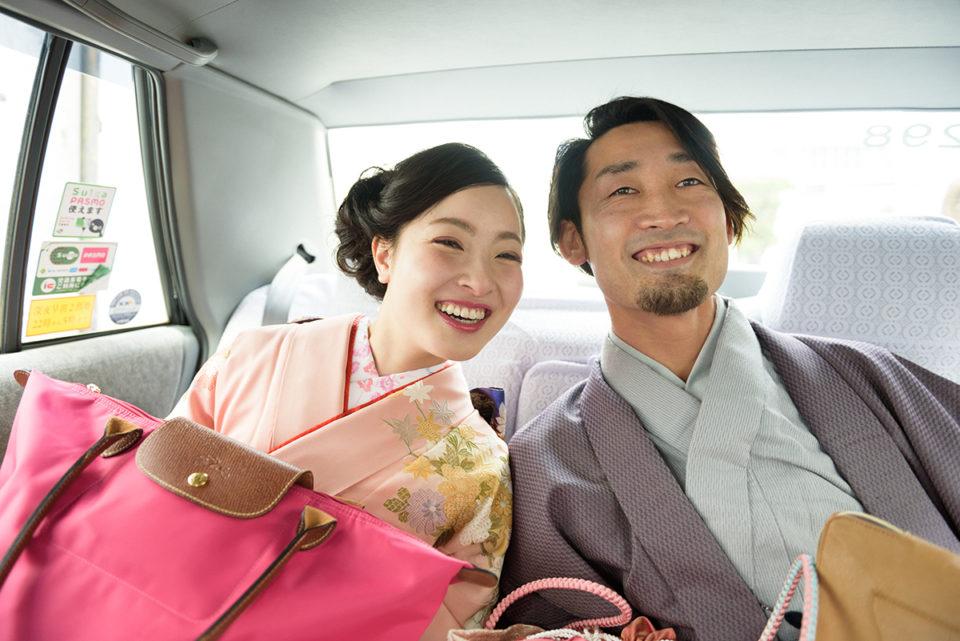 披露宴会場に向かうタクシーの中で笑う新郎新婦