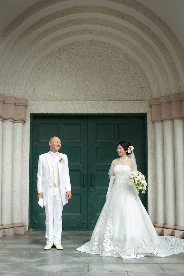 サレジオ教会の緑の扉の前に立って見つめ合う新郎新婦