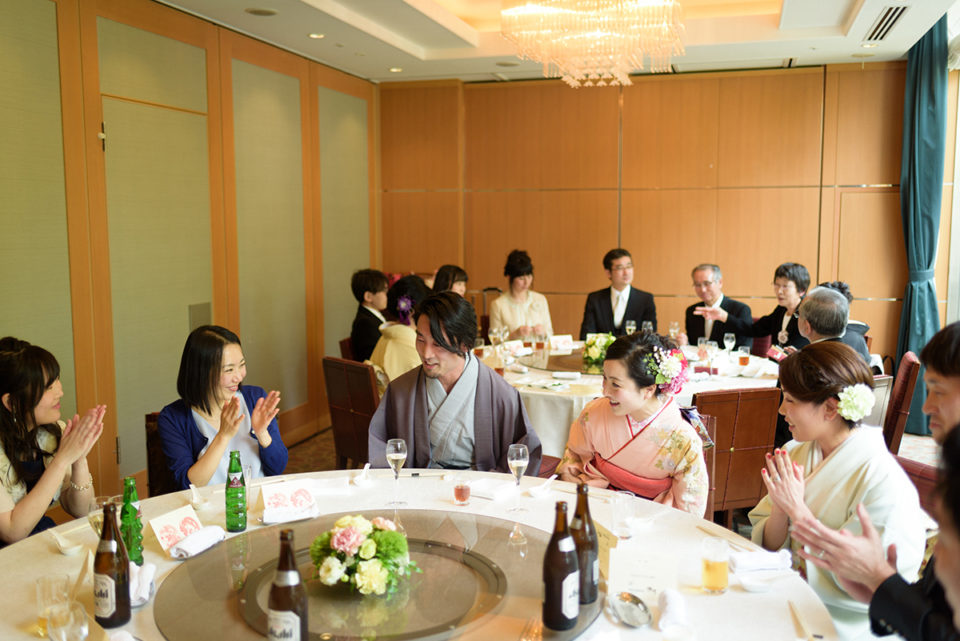 テーブルにやってきた新郎新婦を拍手で迎えるゲストたち
