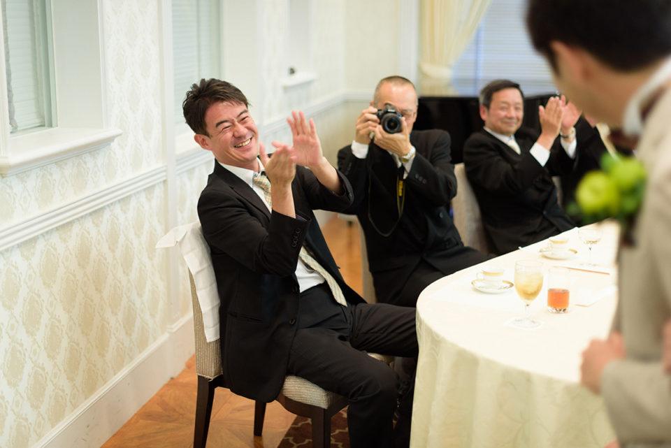 退場する新郎新婦に笑顔で拍手を送る男性ゲスト