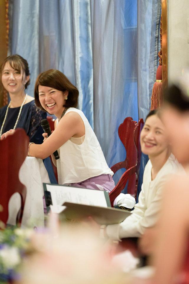 新婦を笑顔で見つめながら思い出を語る女性ゲスト