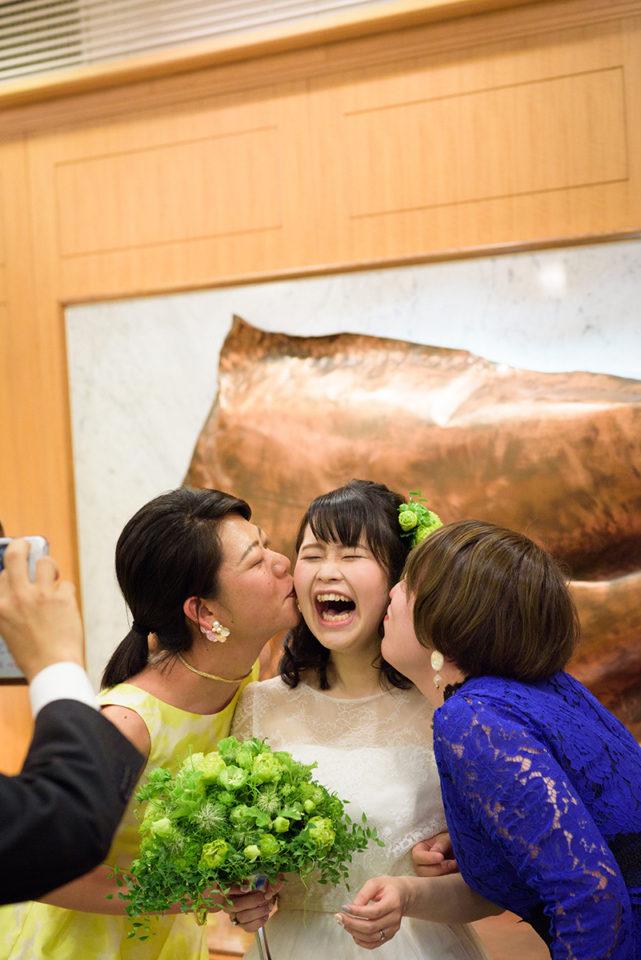 友人に頬にキスをされて笑う新婦