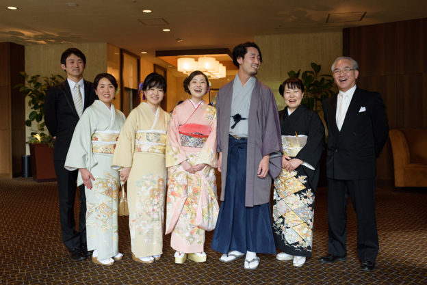 家族写真撮影中に吹き出す新郎新婦と家族