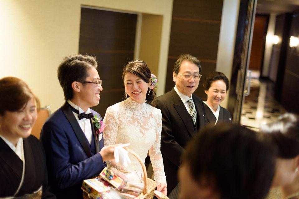 送賓中に笑う新郎新婦と両親