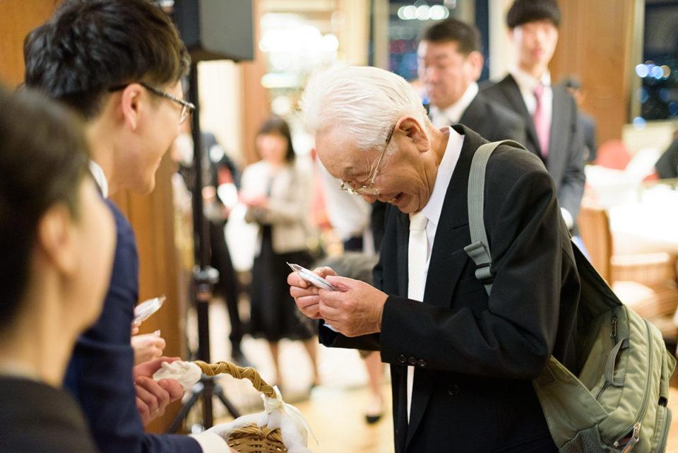 プチギフトを嬉しそうに覗きこむおじいちゃん