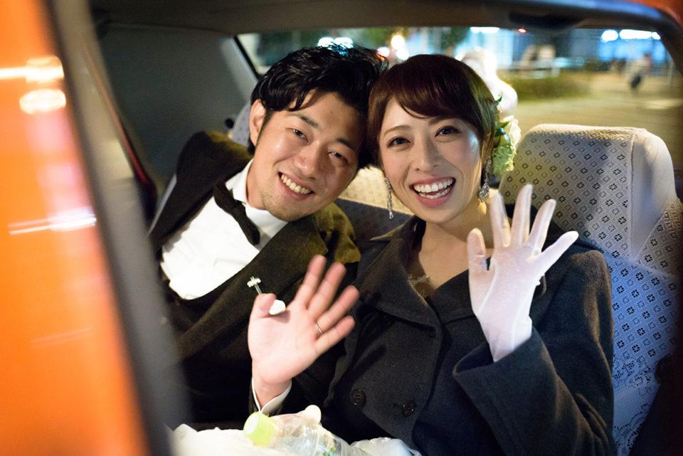 二次会後にタクシーに乗って手を振る新郎新婦