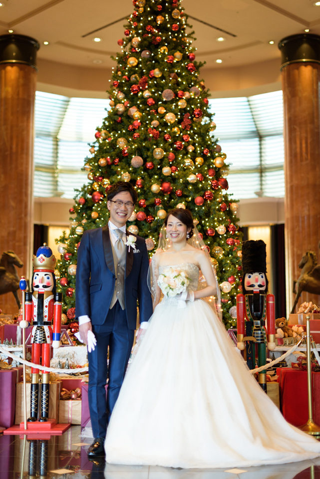 ウェスティンホテル東京のクリスマスツリー前で記念撮影をする新郎新婦