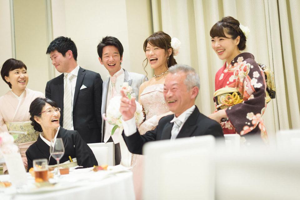 家族と記念撮影をしながら大笑いする新郎新婦