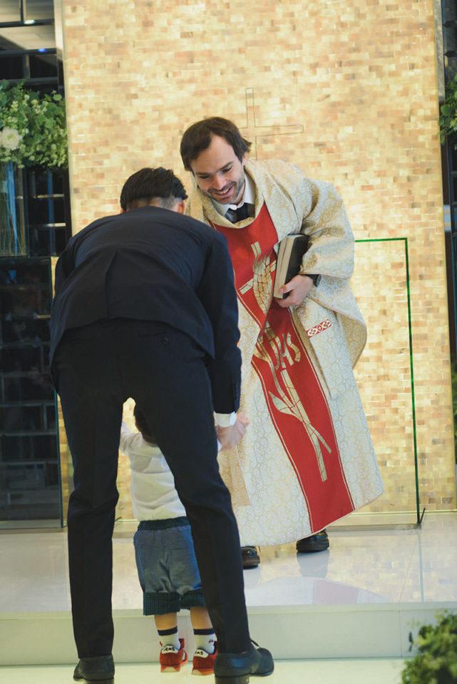 男の子から証明書を受けとる牧師
