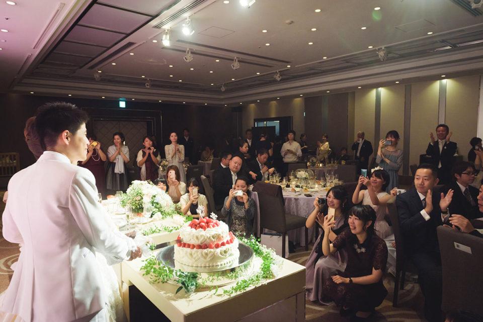 ケーキカットをする新郎新婦を囲むゲストたち