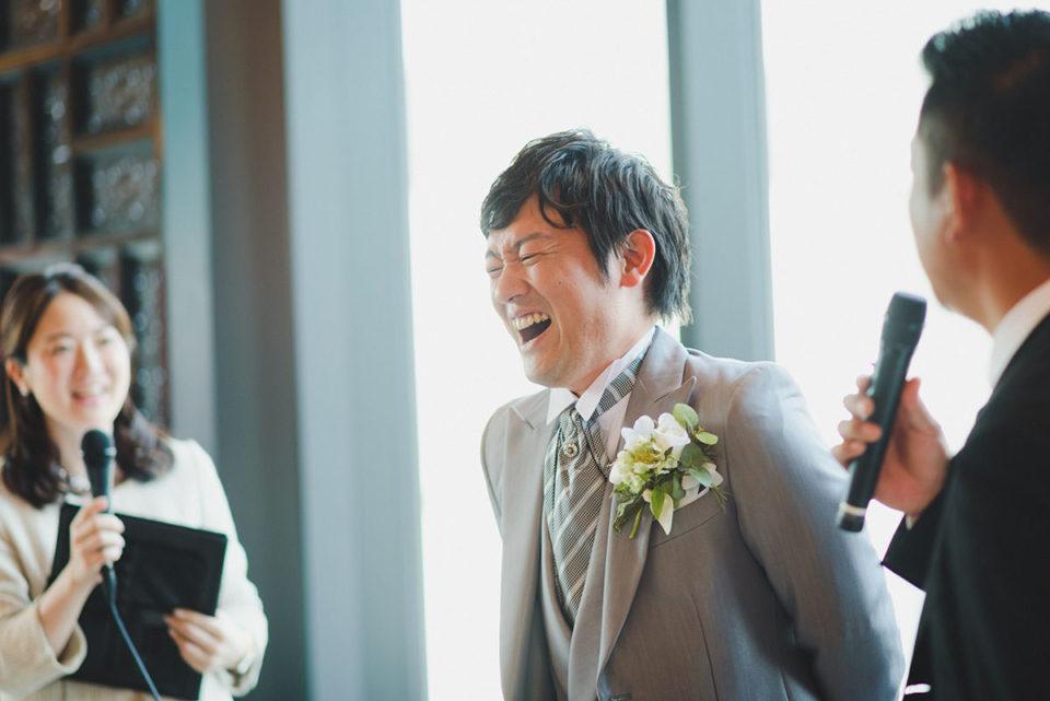 お兄さんのスピーチで笑う新郎
