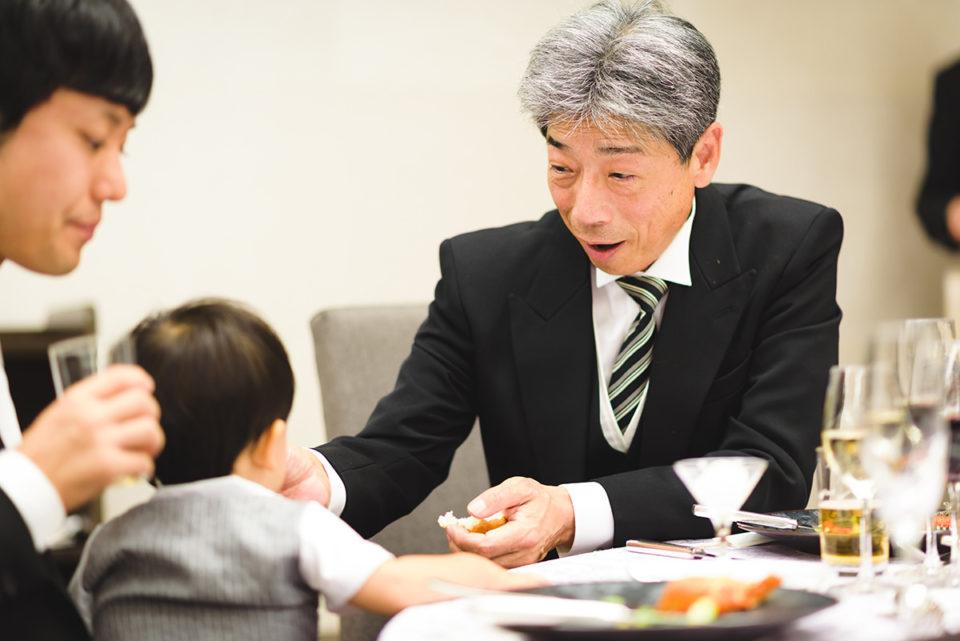 孫にパンをあげる新郎のお父さん