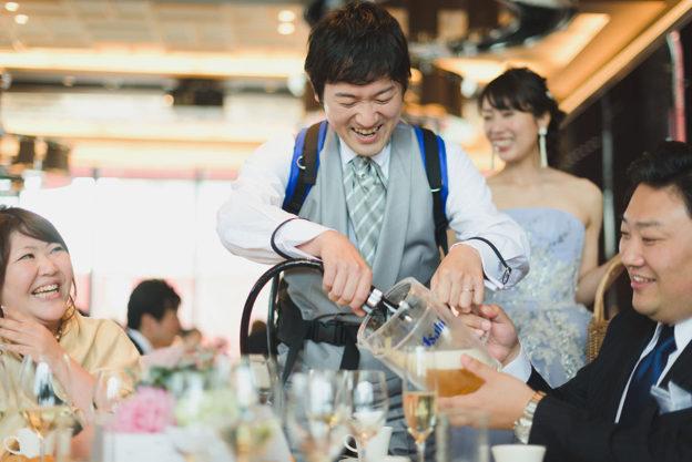 フォトラウンドでテーブルのピッチャーにビールを注ぐ新郎