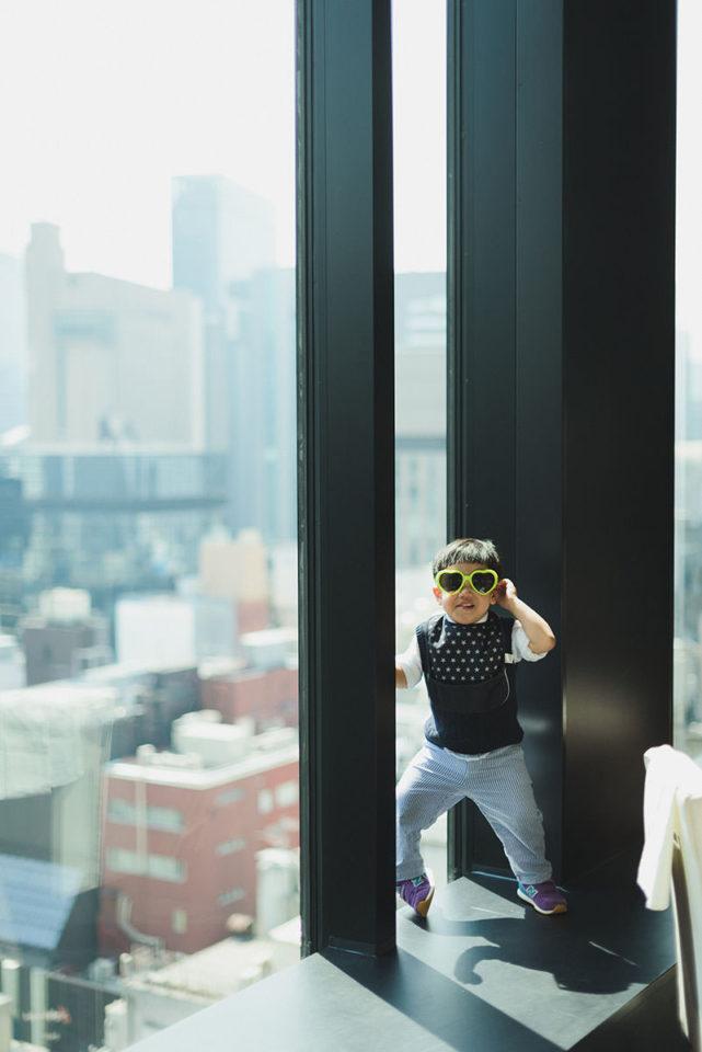 サングラス姿で窓際に立つ男の子
